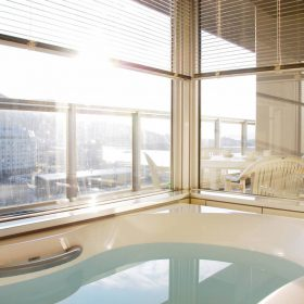 <p>ビューバスを完備。屋外の景色を愉しむことが可能 *外からの視界を遮るためにブラインドを設置しております *現在、他ホテルが建設中のため一部眺望が異なります </p>